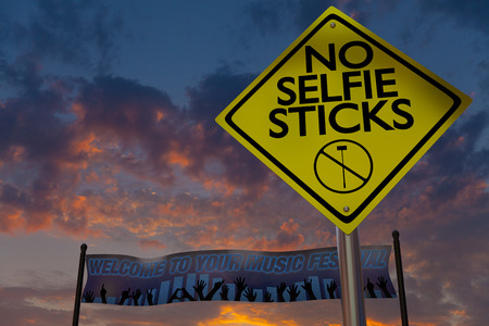 phone ban: A no selfie sticks sign rises above a banner welcoming guests to a music fetival with a sunset in the background.