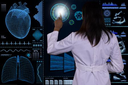 signos vitales: Un doctor de sexo femenino interactúa con un ordenador de vidrio flotante futurista.