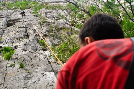 belaying: One man is climbing on a rock wall and an other is belaying for his security.