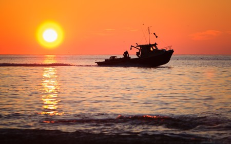 A lobster fishing boat is going to fetch his trap at early morning in Gaspesie, Quebec, Canada Standard-Bild