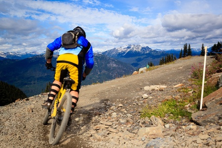 A biker is going to a downhill ride in the rocky mountains