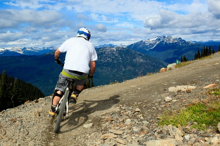 A biker is going to a downhill ride in the rocky mountains  Redakční