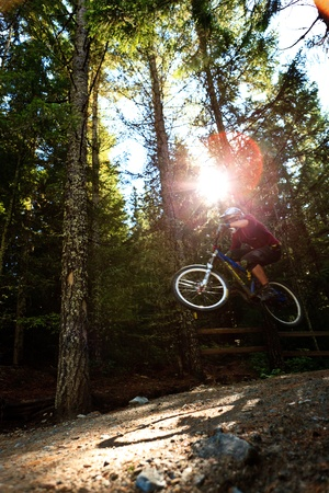 mountain biking: Motion blurred montain biker is jumping during a downhill ride.