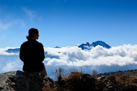 A woman is sitting, looking the mountain peak over the clouds.