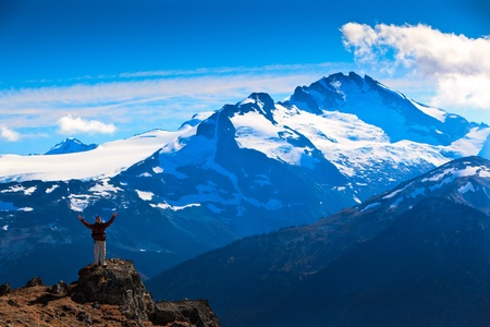 A woman is standing on a rock In front of some magnificent mountains. photo