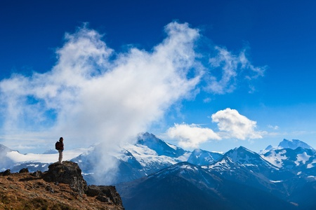recreational area: A woman is standing on a rock overlooking  the canadian rocky mountains when a cloud is going up the cliff just in front of her.
