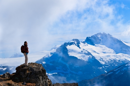 A woman is standing on a rock overlooking  the canadian rocky mountains. photo