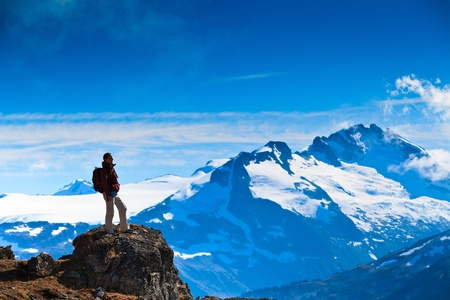perseverance: A woman is standing on a rock overlooking  the canadian rocky mountains.