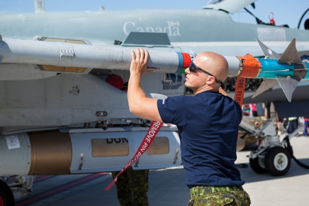 f 18: Bagotville, Canada- June 22, 2013: The Bagotville Airshow is a 2 days airshow where the Bagotville Airport opens to the public with a variety of aerial performers as well as aircraft and vehicles on display. This image shows a technician checking a missil Editorial