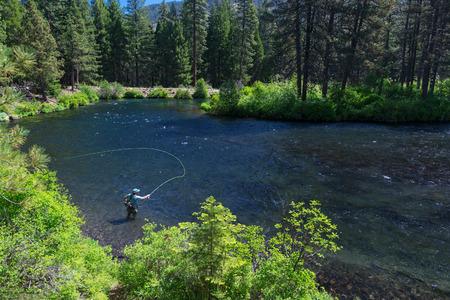 Vlieg visser werpt in het heldere water van de rivier de Metolius.