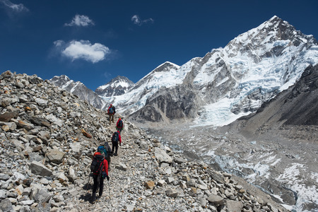 grandiose: Trekkers hike along a trail amongst the grandiose mountains of the Himalayas. Stock Photo