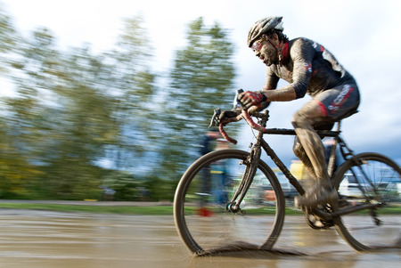 A muddy, energized, and determined cyclocross racer riding through a mud puddle.