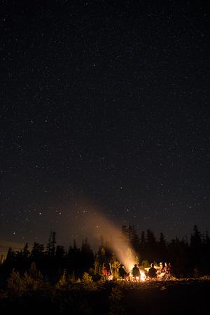 Un grupo de amigos que conversan en una fogata en las montañas bajo el cielo lleno de estrellas.