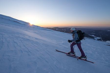skinning: Adventurous female skier skinning up the mountainside at sunrise.