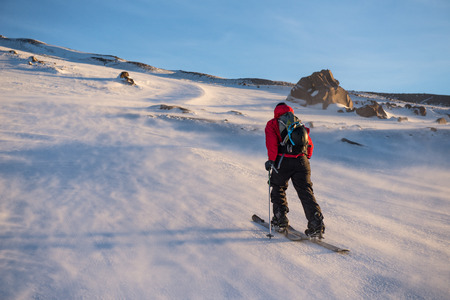 남성 모험가 splitboard에 바람 불고 산 중턱을 껍질.