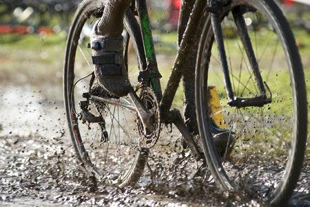 공기에서 뿌려 놓은 진흙을 타고 타는 자전거 타는 사람.