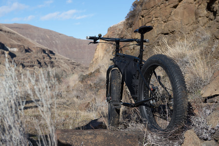Mountain bike propped up along a rock in the mountains Stock Photo