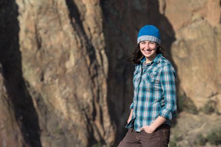 젊은 여자는 미소 하 고 우연히 흐리게 산 절벽 벽 배경 앞에 서.