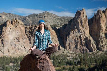 바위에 인도 스타일 앉아 젊은 여자는 산악 배경 사이 meditates.