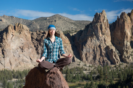 A young woman sitting indian style on a rock meditates amongst a mountainous backdrop.