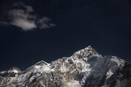 히말라야 산, 산. 에베레스트 (Everest)와 로체 (Lhotse)는 별이 가득 찬 하늘 아래 달에서 밝게 빛납니다. 스톡 콘텐츠