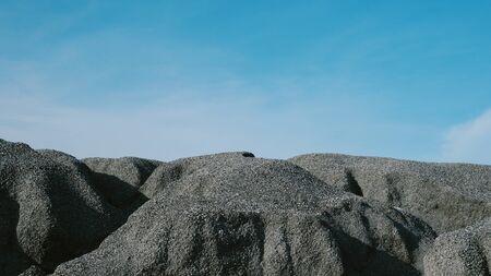 Crushed stone mountain against blue sky background Standard-Bild
