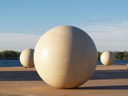 Three white concrete spheres in a park with side lighting         Stock Photo