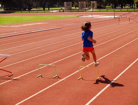 young girl jumping small hurdles on track