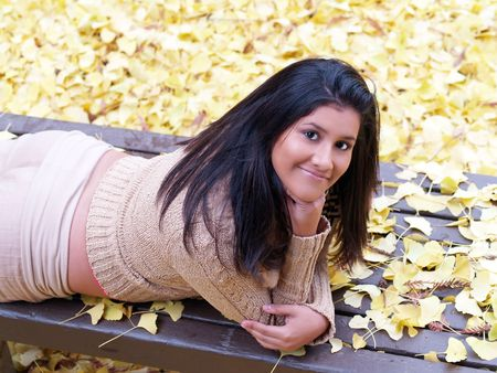 young latina girl on stomach on bench with autumn leaves         Stock fotó
