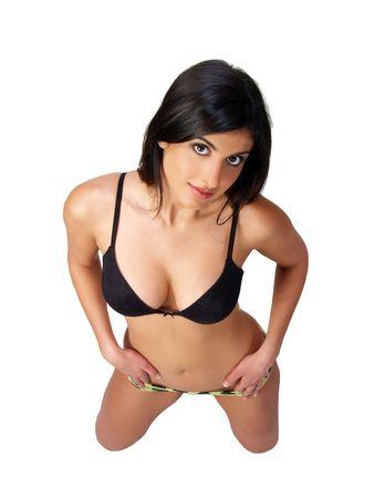 Young woman in black bikini top kneeling