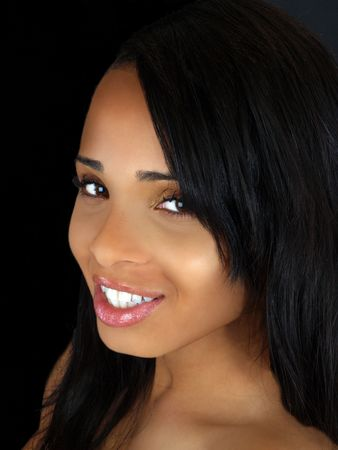 Smiling portrait of young black woman with dark background