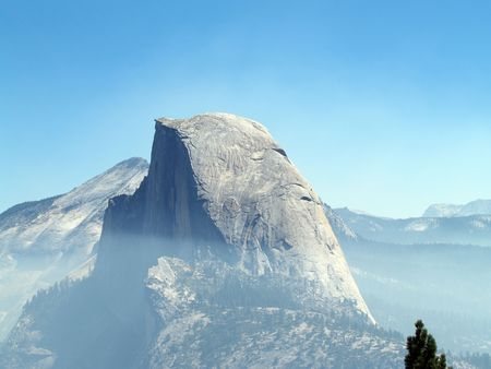 Smoke haze up to Half-dome in park from nearby fire