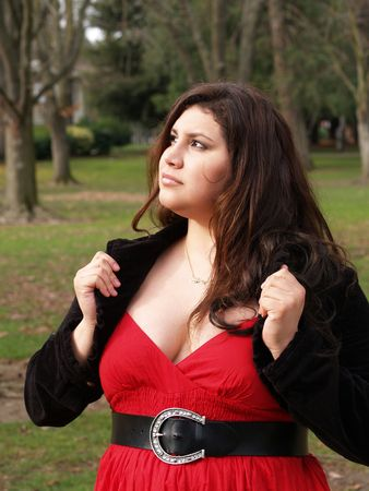 plus-size woman outdoors in jacket and red dress       Фото со стока
