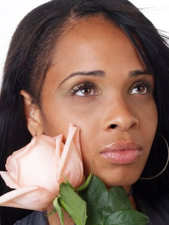 Portrait of young black woman with pink rose to cheek Фото со стока