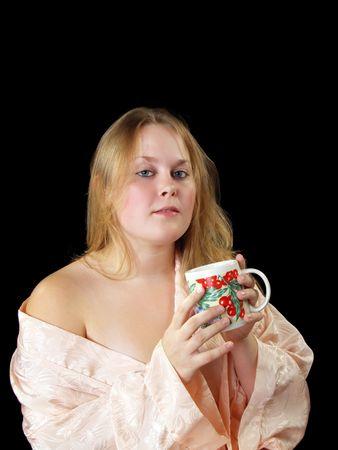 Jonge vrouw in perzik gewaad met koffie of thee beker