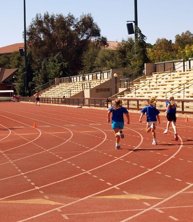 three young girls in shorts and shirts running on track