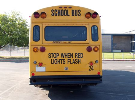 school buses: back of yellow bus parked on school grounds