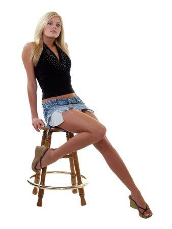 escabeau: Jeune femme en jupe jeans montrant les pieds nus     Banque d'images
