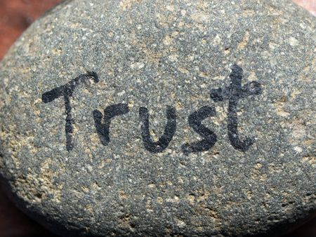 small rock in natural light with word trust written on it
