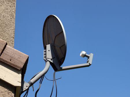 satelite: Plato de sat�lite de casa contra el lado de cielo azul de casa  Foto de archivo