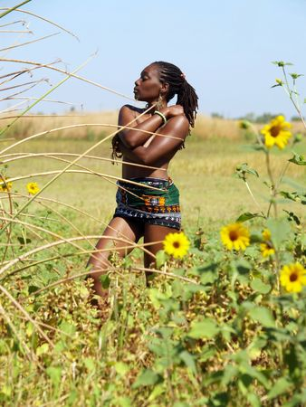 Topless black woman outdoors green grass yellow flowers blue sky