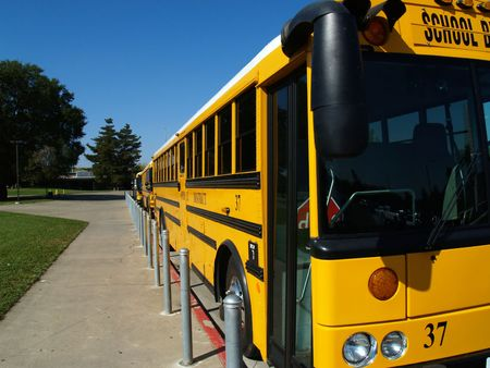 Three school buses parked along curb in parking lot          Stock fotó