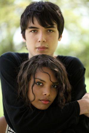 Young caucasian teen boy and mixed teen girl outdoor portrait