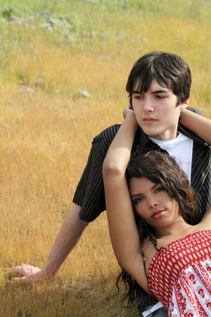 Young teen couple reclining in the grass