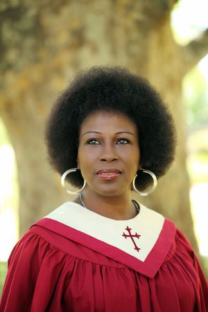 African American female preacher in robes outdoors Stock Photo