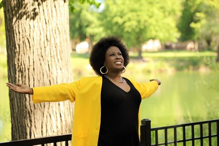 African American woman outdoors yellow jacket arms spread wide Stock fotó