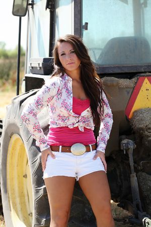 Young teen girl in shorts leaning against tractor outdoors