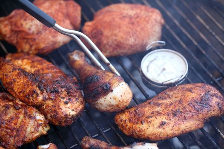 thermometer fork pieces of chicken cooking on grill