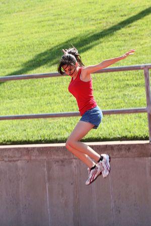 latina teen: Young latina teen girl jumping down from wall