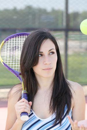 latina teen: young latina teen girl tossing tennis ball and holding racket Stock Photo